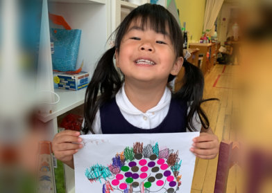 child showing off her art